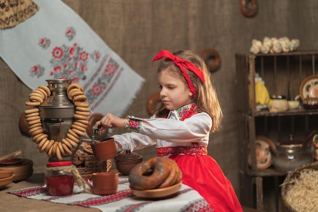 Meisje dat rode hoofdband en sieroverhemd het gieten thee van samovar draagt die maslenitsa viert