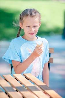 Meisje dat roomijs in openlucht bij de zomer in openluchtkoffie eet
