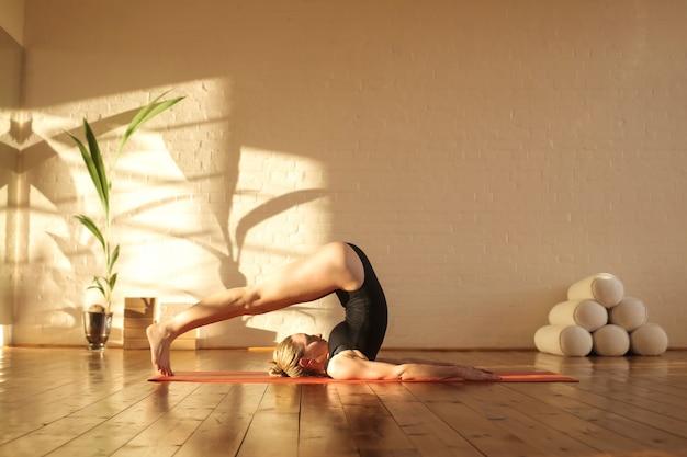 Meisje dat sommige pilatesposities in een mooie studio uitoefent
