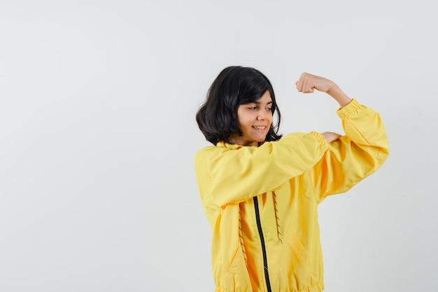 Meisje dat spieren van de arm in gele hoodie toont en zelfverzekerd, vooraanzicht kijkt.