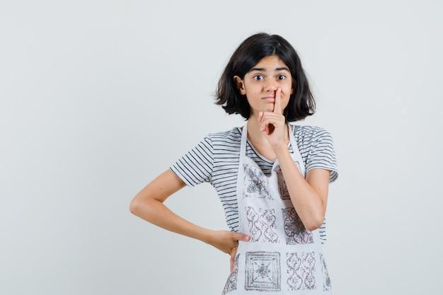 Meisje dat stilte gebaar in t-shirt, schort toont en voorzichtig kijkt.
