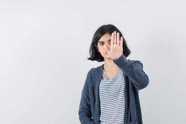 Meisje dat stopgebaar in t-shirt, jasje toont en geïrriteerd kijkt
