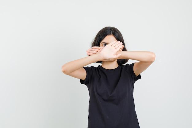 Meisje dat stopgebaar in zwart t-shirt toont en bang, vooraanzicht kijkt.