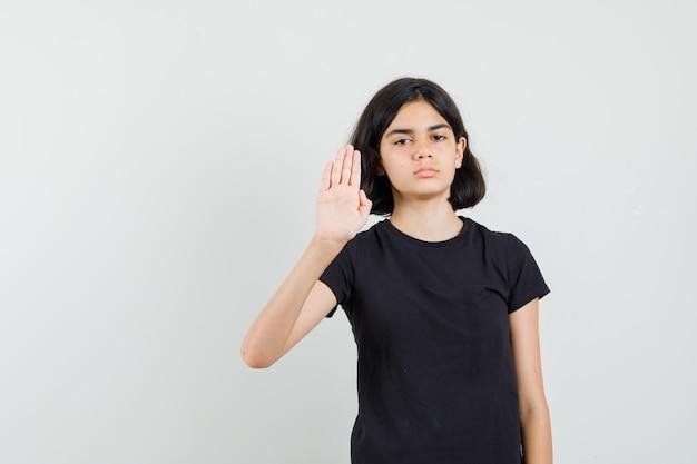Meisje dat stopgebaar in zwart t-shirt toont en geïrriteerd, vooraanzicht kijkt.
