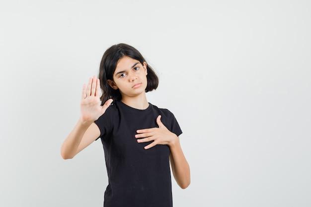 Meisje dat stopgebaar in zwart t-shirt toont en moe, vooraanzicht kijkt.