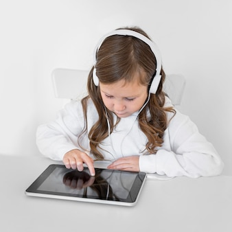 Meisje dat tablet met hoofdtelefoons gebruikt