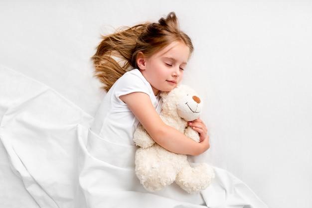 Meisje dat teddybeer koestert die op bed legt