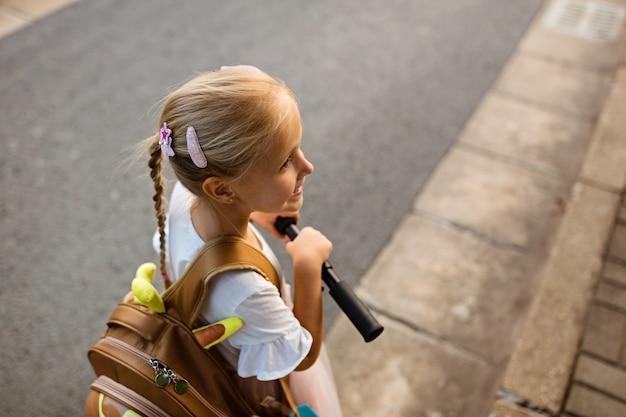 Meisje dat terug naar huis na school met schooltas loopt