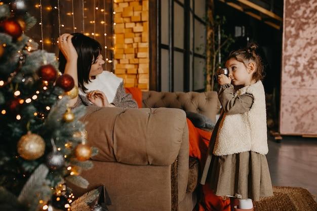 Meisje dat thuis foto's van haar moeder maakt, naast een kerstboom