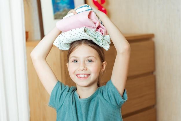 Meisje dat thuis gevouwen kleren in zijn handen houdt