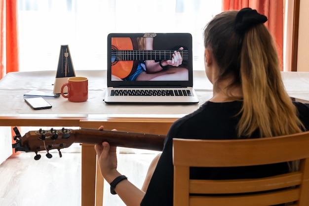 Meisje dat thuis gitaarlessen bestudeert