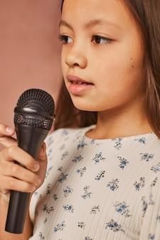 Meisje dat thuis leert zingen met microfoon