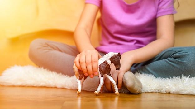 Meisje dat thuis met een stuk speelgoed paard speelt