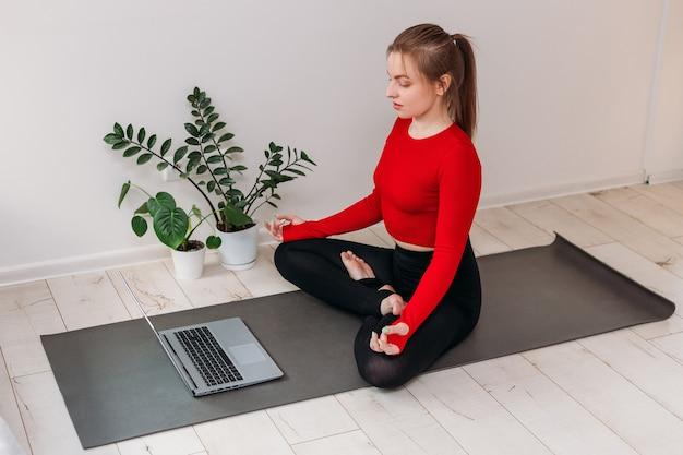 Meisje dat thuis yoga beoefent. vrouw kijkt naar video op internet en herhaalt de taken. binnen en buiten trainen. sport en gezond actief levensstijlconcept.