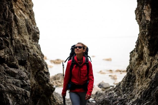 Meisje dat tussen de rotsen op de kustlijn op het overzees met wandelingsrugzak loopt