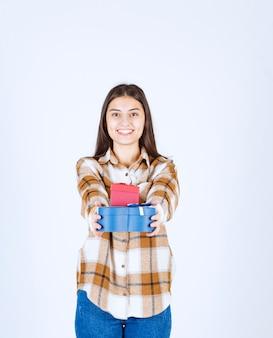 Meisje dat twee geschenken op een witte muur weggeeft.