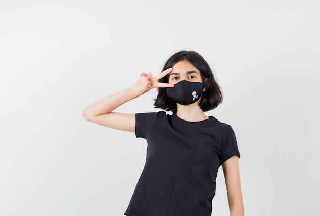 Meisje dat v-teken dichtbij oog in zwart t-shirt, masker vooraanzicht toont.