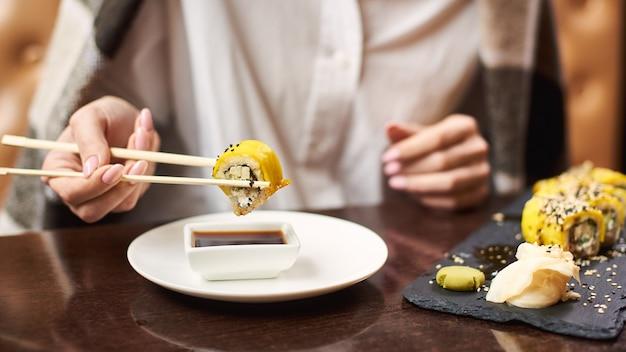 Meisje dat van aziatische schotel met sojasaus geniet die voedselstokken gebruikt.