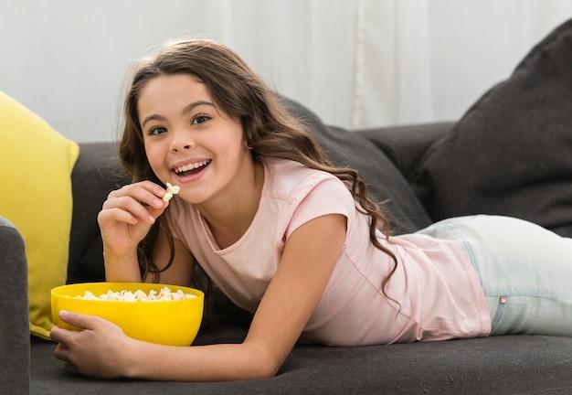 Meisje dat van een kom popcorn geniet