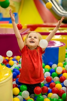 Meisje dat van kleurrijke ballenkuil geniet