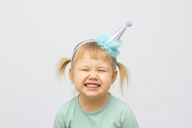 Meisje dat van succes geniet tegen een grijze achtergrond. aanbiddelijk klein meisje dat in blauw t-shirt overwinning viert