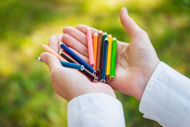 Meisje dat vele kleurrijke houten potloden in de handen houdt.