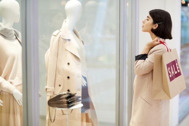 Meisje dat venstervertoning bekijkt in winkelcomplex