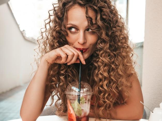 Meisje dat verse smoothie in plastic kop met stro drinkt