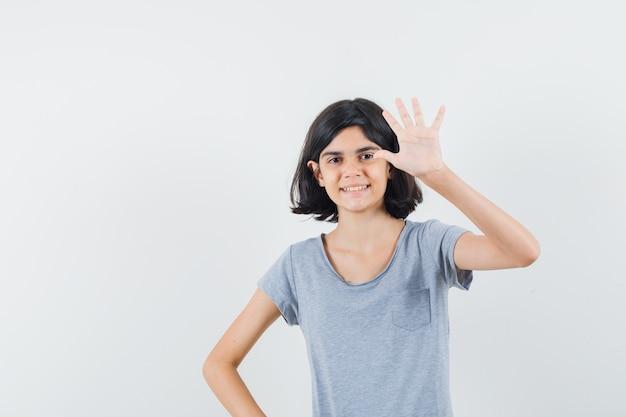 Meisje dat vijf vingers in t-shirt toont en zelfverzekerd, vooraanzicht kijkt.