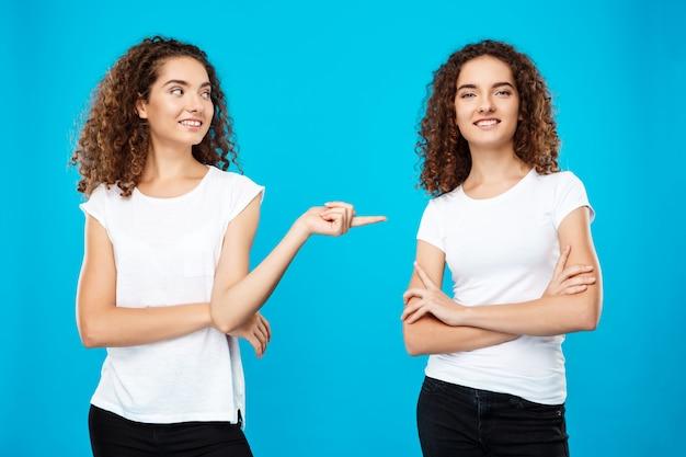 Meisje dat vinger richt op haar zusterstweeling over blauwe muur