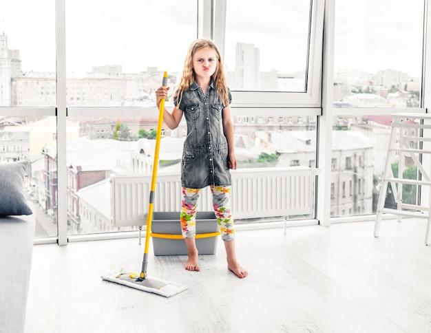Meisje dat vloer in de woonkamer dweilt
