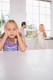 Meisje dat voor de vechtende ouders onderdrukt kijkt