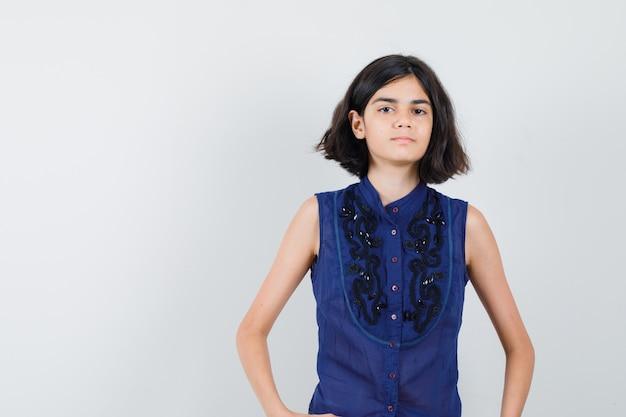 Meisje dat voorzijde in blauwe blouse bekijkt en ernstig kijkt.