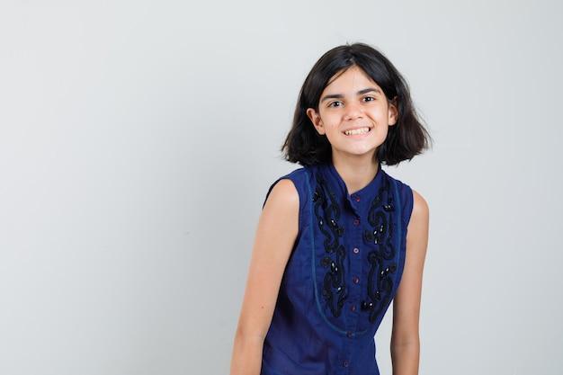 Meisje dat voorzijde in blauwe blouse bekijkt en gelukkig kijkt.