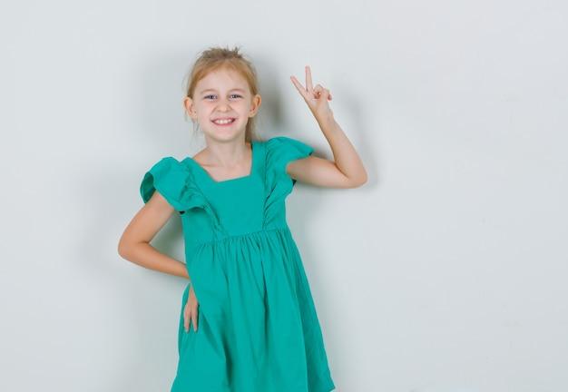 Meisje dat vredesgebaar in groene kleding toont en vrolijk kijkt. vooraanzicht.