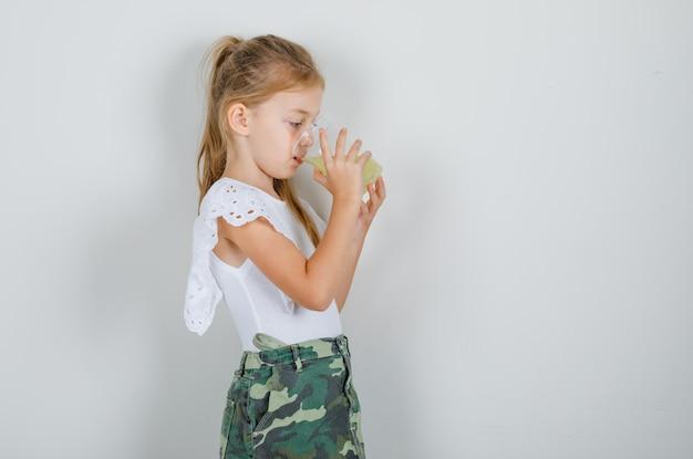 Meisje dat vruchtensap in wit t-shirt drinkt