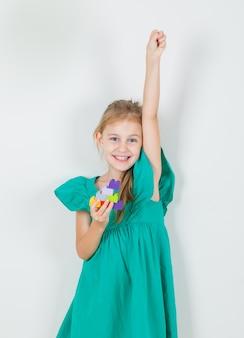 Meisje dat vuist met stuk speelgoed blokken in groene kleding opheft en vrolijk kijkt
