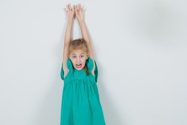 Meisje dat wapens met open mond in groene kleding opheft