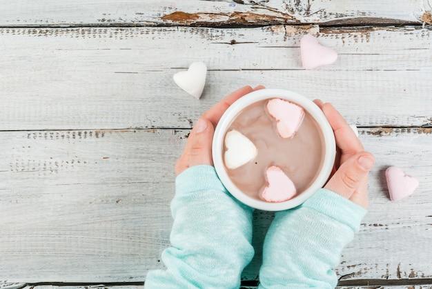 Meisje dat warme chocolademelk met de harten van de heemst drinkt