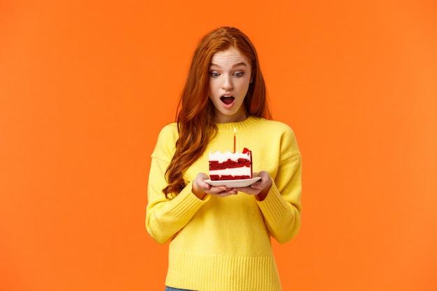 Meisje dat wens maakt, verjaardagstaart met één kaars ontvangt