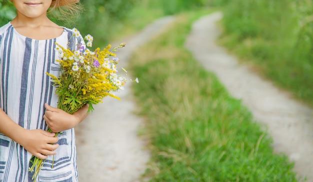 Meisje dat wilde bloemen in de handen van een kind houdt