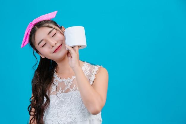 Meisje dat witte pyjama draagt die een papieren zakdoekje in de hand op het blauw houdt.