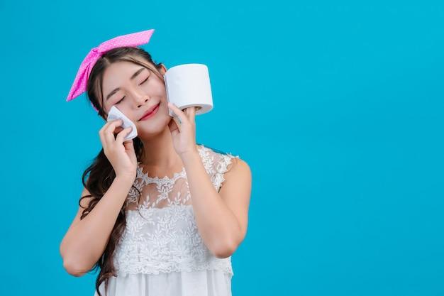 Meisje dat witte pyjama draagt die papieren zakdoekje op haar gezicht op een blauw gebruiken.
