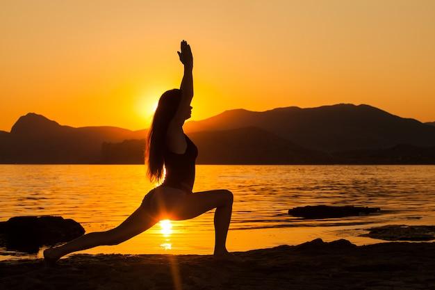 Meisje dat yoga doet door de oceaan.