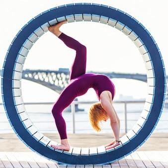 Meisje dat yoga in een ring op het strand doet