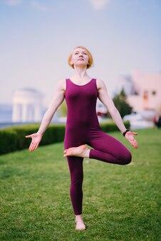 Meisje dat yoga op groen gras op een zonnige dag doet