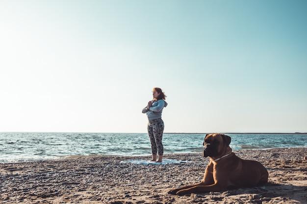 Meisje dat yoga op het strand met haar hond doet
