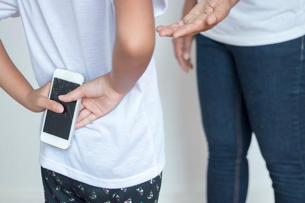 Meisje dat ze niet accepteert dat de mobiele telefoon van de moeder kapot was.