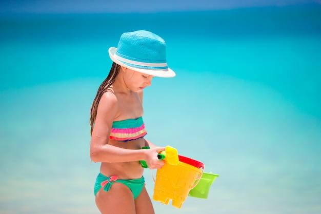 Meisje dat zeeschelpen op wit zandstrand verzamelt