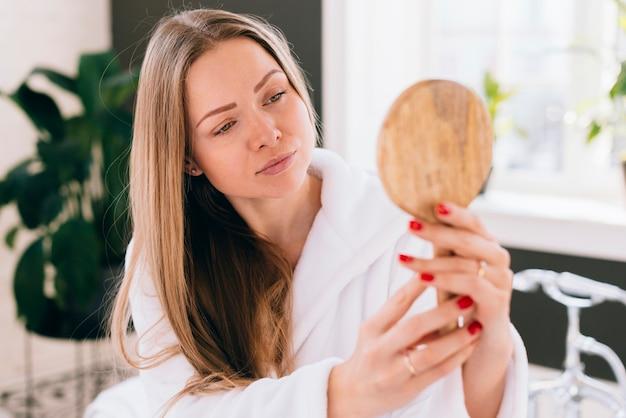 Meisje dat zelf een spiegel bekijkt